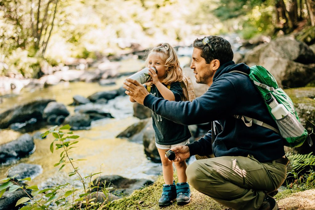 A father and daughter hiking near a stream in Maine.