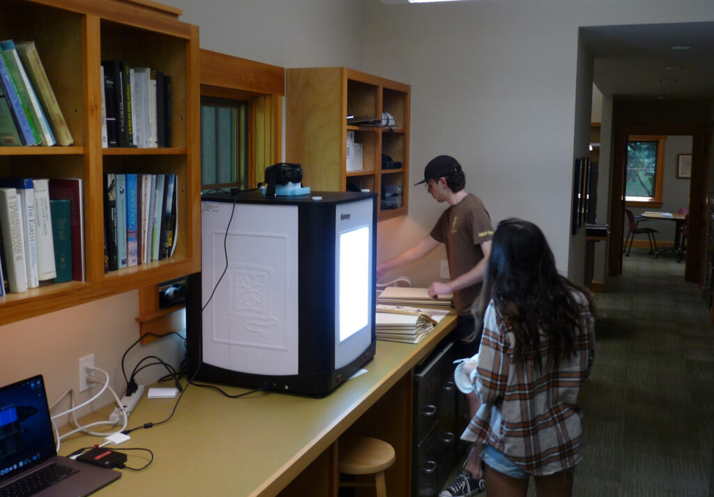 Two students work in an open office and around a large light box and mounted camera. Highstead's Herbarium.